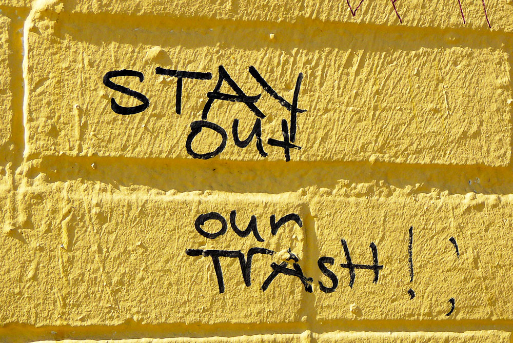 Tagging on wall reads 'Stay out our trash'