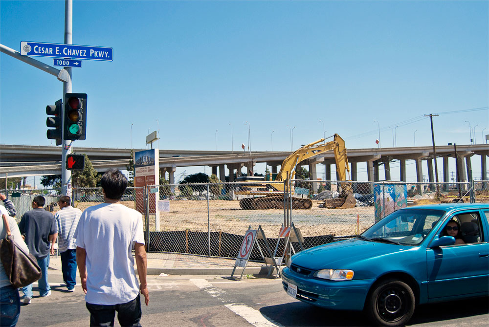 Image of people walking towards the Chicano Park Day celebration with construction of El Mercado in background.